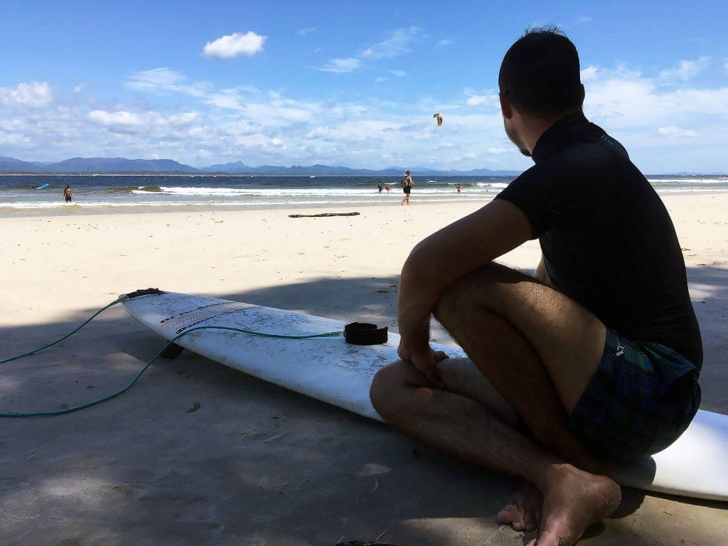 Berti am Strand von Byron Bay auf Surfboard